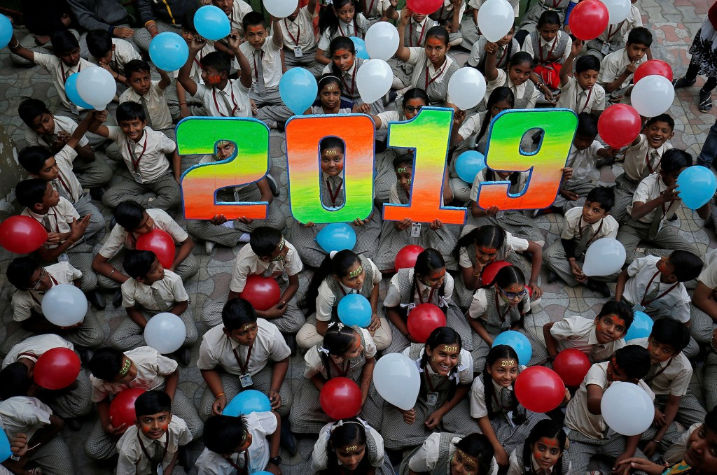 Schoolchildren hold balloons as they pose during celebrations to welcome the New Year at their school in Ahmedabad, India, December 31, 2018. REUTERS/Amit Dave
